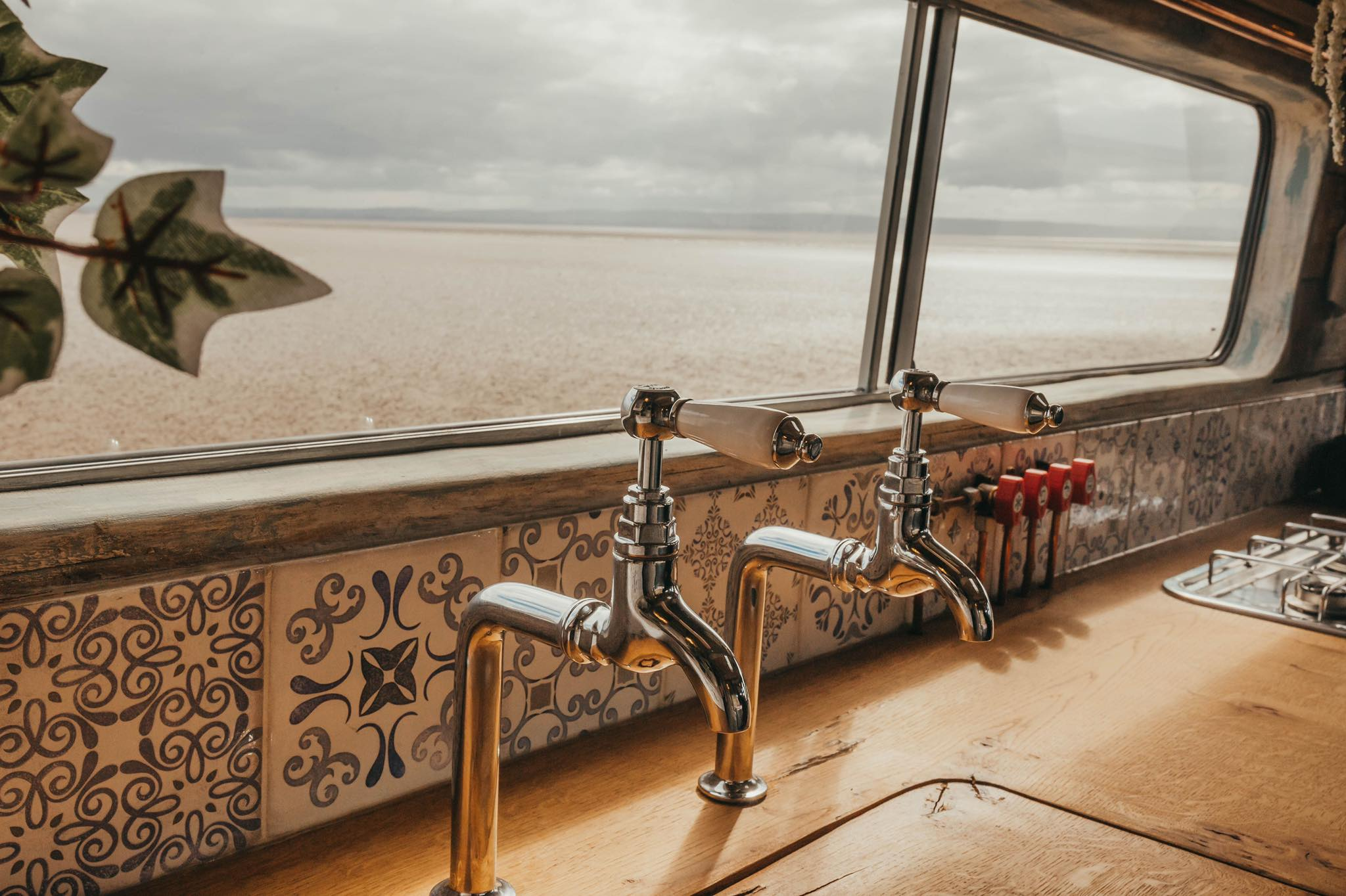 an interior view of Ernie the campervan kitchen overlooking a beach